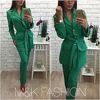Красивый женский костюм делового стиля: удлиненный пиджак и брюки, зеленый