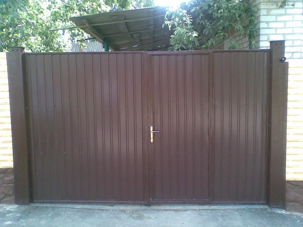 На фотографии представлены ворота из профнастила с врезной калиткой нашего производства. Профнастил с высотой профиля 10мм, цвет - шоколад (8017). Ворота были установлены на существующие столбы заказчика.