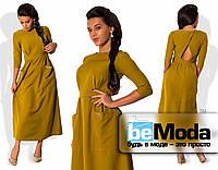 Привлекательное женское платье длиной ниже колен с оригинальным вырезом на спинке и большими накладными карманами горчичное