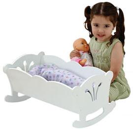 Деочка возле кроватки, люльки с куклой