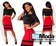 Эффектный женский костюм из укороченного черного топа по фигуре и цветной юбки с черными горизонтальными полосами красный