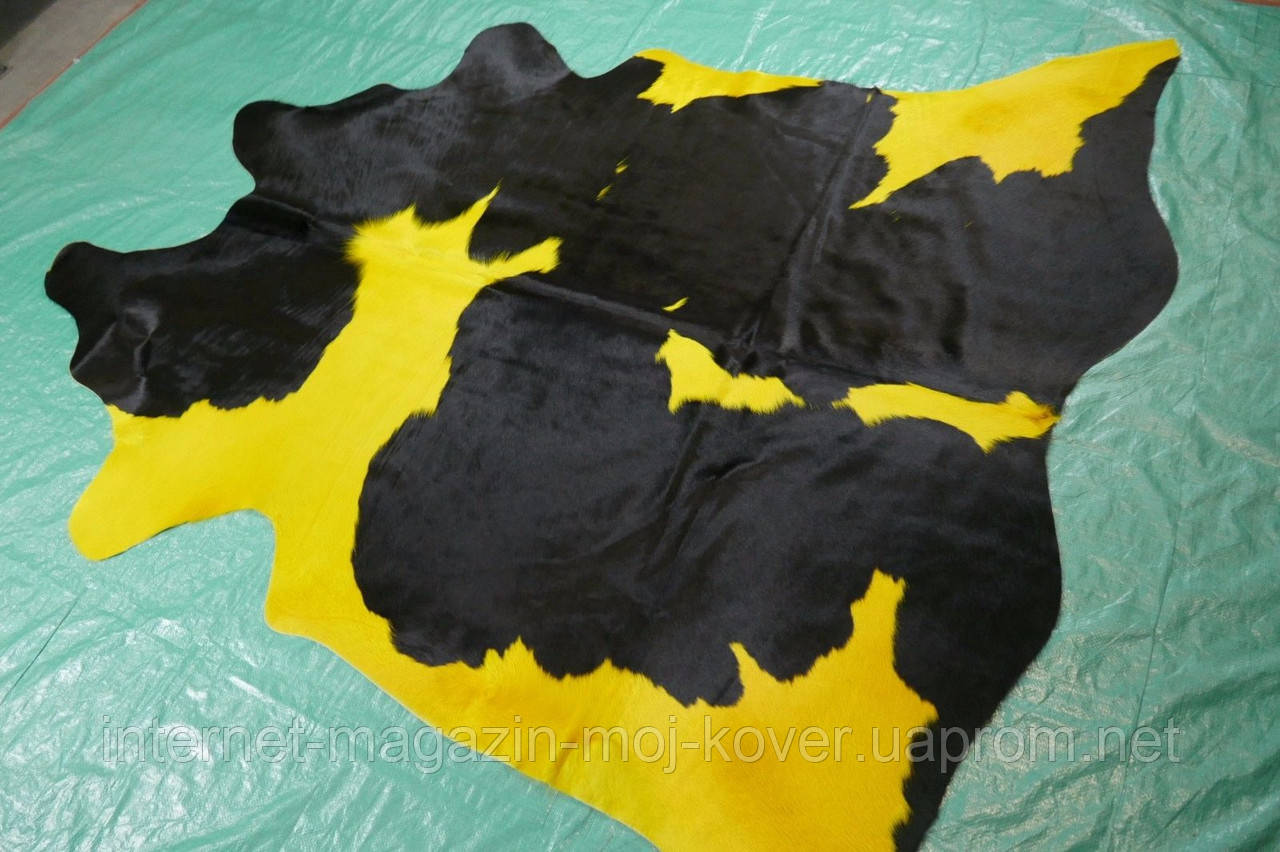 Необычная яркая коровья шкура ярко желтого цвета с черными пятнами