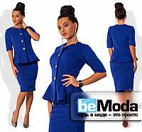 Деловой женский костюм из пиджака с короткими рукавами, широкой баской, блестящими пуговицами и приталенной юбки длиной до колен синий