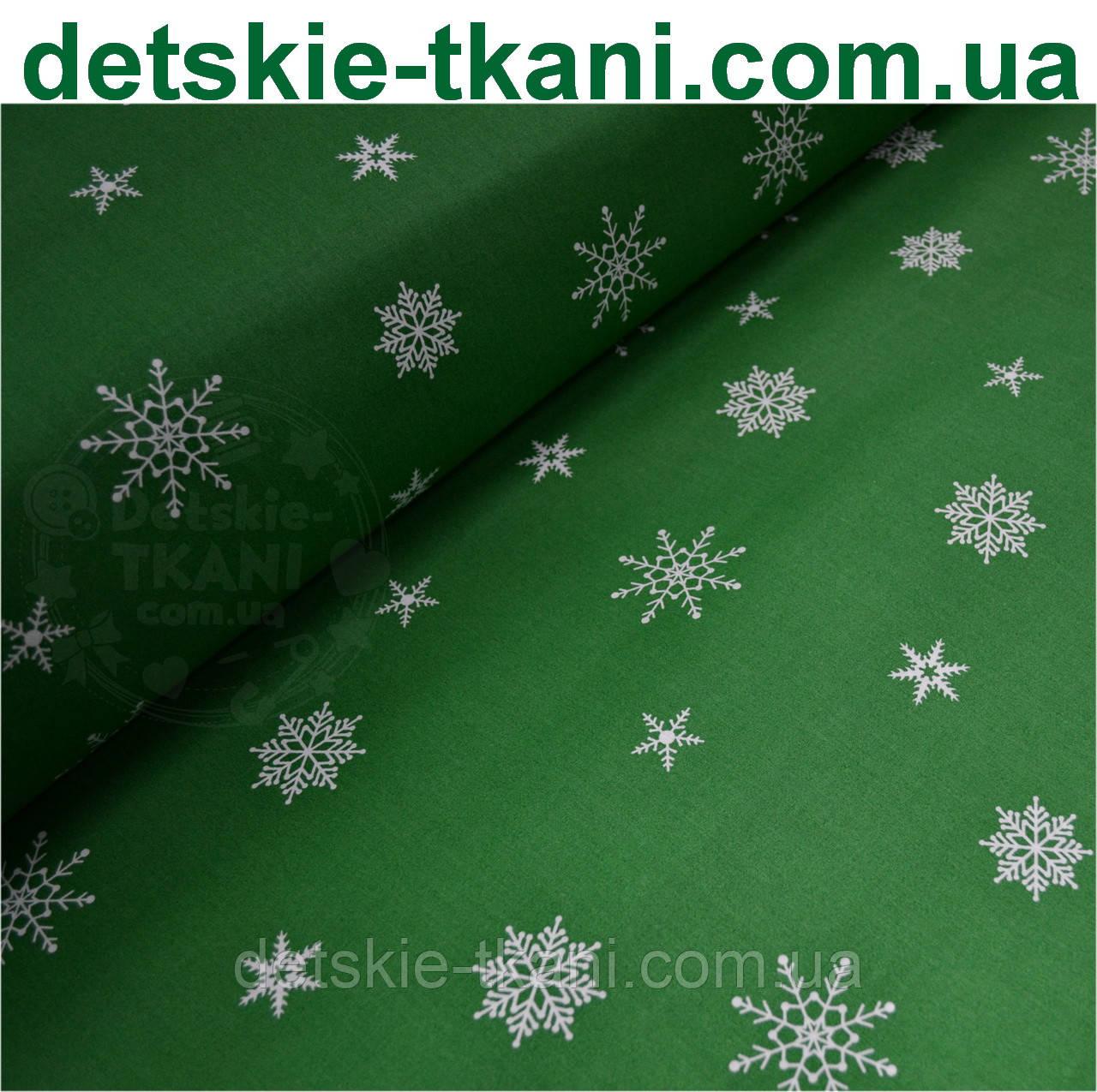 Ткань хлопковая с редкими снежинками на зелёном фоне № 447