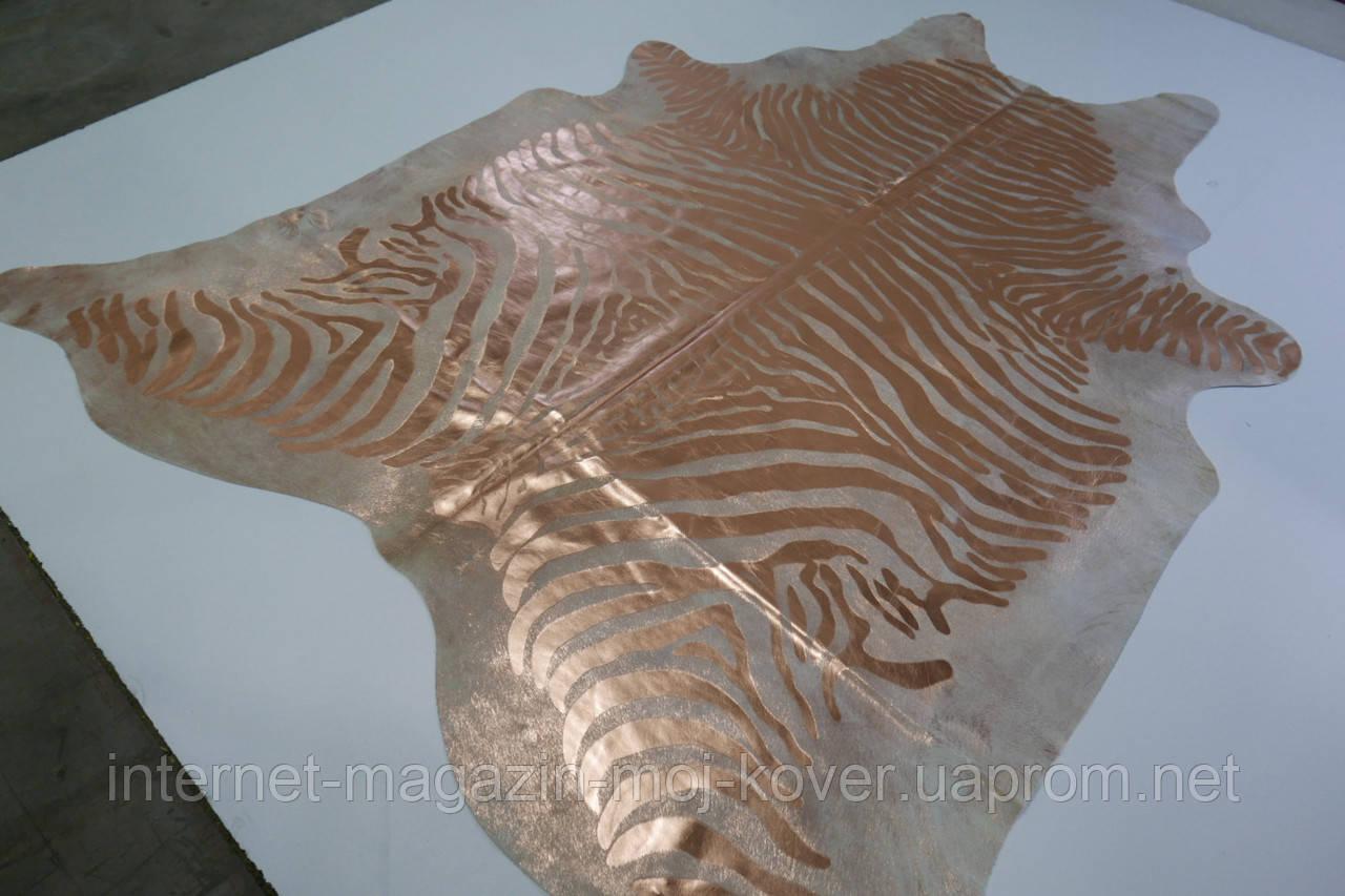 Незвичайна шкура корови пофарбована в зебру золотою фарбою на бежевому фоні