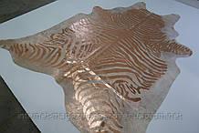Необычная шкура коровы покрашенная в зебру золотой краской на бежевом фоне