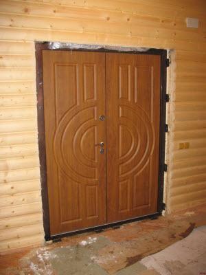 Полуторная дверь, закреплена монтажными пластинами к рубленому дому.