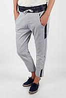 Необычные женские укороченные спортивные брюки простого кроя с карманами по бокам и контрастными вставками на поясе светло-серые