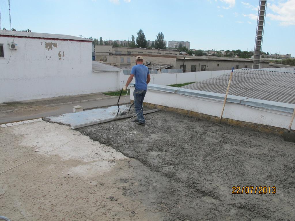 Равномерное распределение бетона по существующему цементному основанию и выравнивание стяжки виброрейкой.