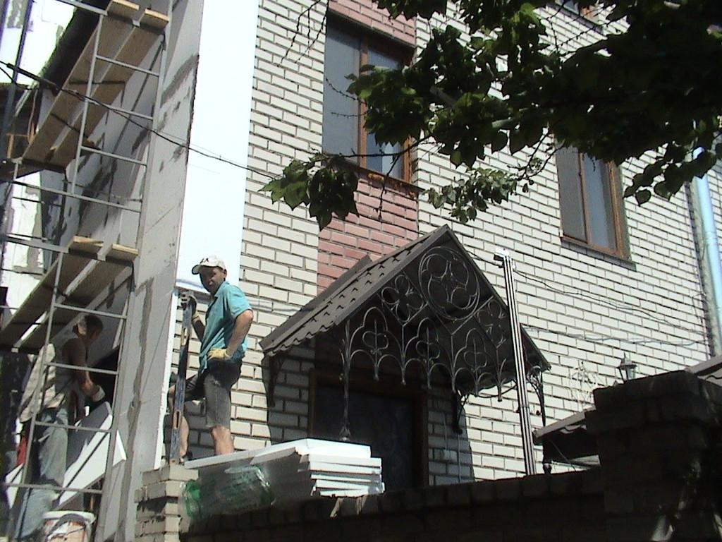 Облицовка кирпичных стен плитами из пенополистирола (пенопласта) толщиной 50 мм с лесов.