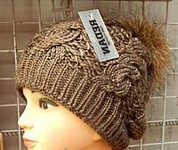 Теплая женская шапка украшена помпоном из меха енота