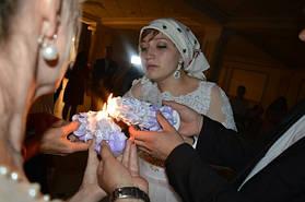 Волнующий момент зажигания свечей семейного очага родителями и молодоженами.