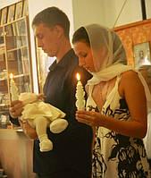 Крестный держит ребенка и свечу, а крестная держит свечу.