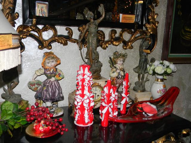 Красные резные свечи на комоде.