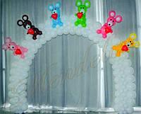 Белая арка из шариков с игрушками