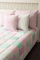 Покрывало с подушками в розово-мятном цвете.