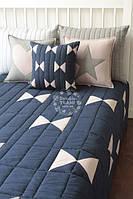 Сине-белое покрывало с подушками.