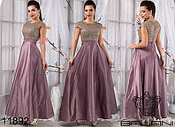 Вечернее платье приталенного силуэта с клешеной юбкой, сверху декорированное оригинальной отделкой из блесток.