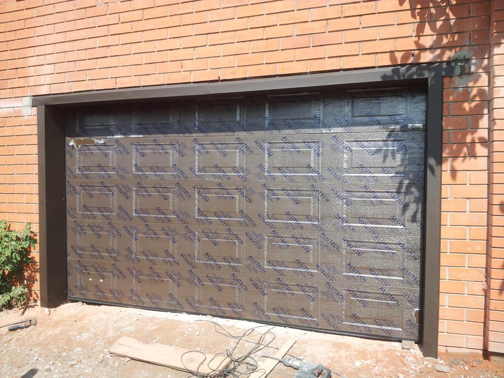 Установка подъемно-секционных гаражных ворот с увеличением и обшивкой проема