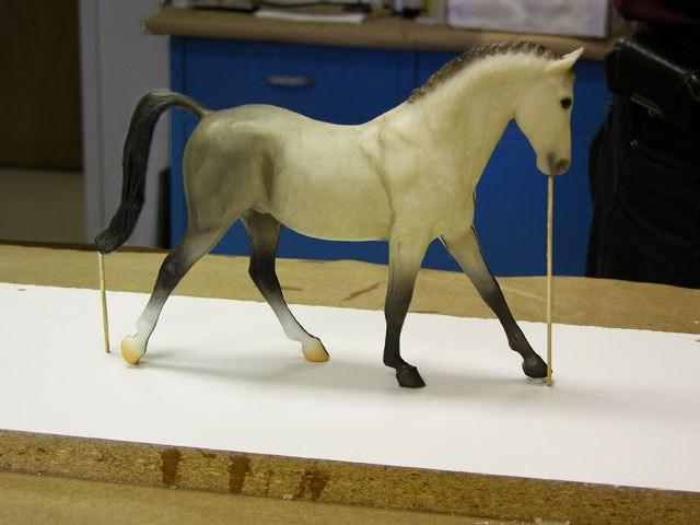Лошадь приклеиваем к основанию подставки клеевым пистолетом и для предотвращения образования пузырьков воздуха делаем 2 вентиляционных отверстия на  кончике хвоста и рта (взяты деревянные палочки)