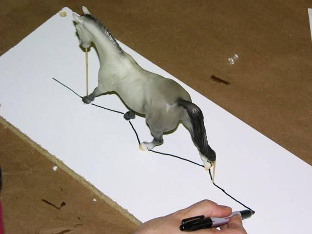 Вторая линия рисуется на основании подставки и является проекцией 1-й линии, нарисованной на животе. Линию нужно продлить минимум на 5 см дальше лошади в обе стороны. Она должна выглядывать за края силиконовой формы