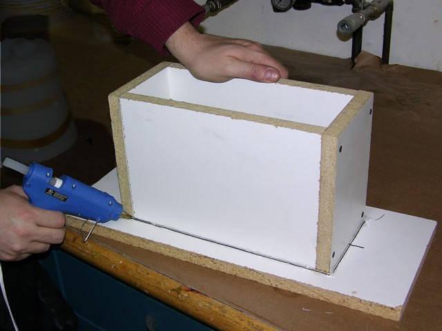 Коробка крепится к основанию подставки с помощью клеевого пистолета. Нужно убедиться, что в коробе нигде нет щелей для предотвращения вытекания силикона