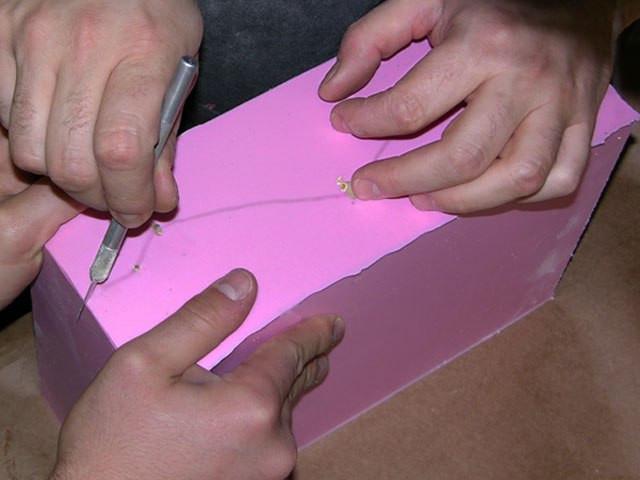 Извлечение модели: линия надреза, проведенная на подставке, отпечаталась на нижней поверхности  силиконовой формы. Сейчас вам понадобится помощник: один раздвигает и держит, другой разрезает