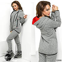 Теплый костюм: кофта и штаны. Кофта асимметричной длины с капюшоном на завязках, декорированная нашивками.