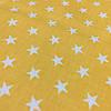 Ткань с белыми звездами на желто-оранжевом фоне