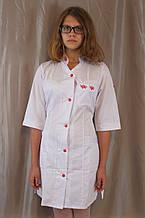 Медицинский женский белый халат с коротким рукавом, украшенный вышивкой.
