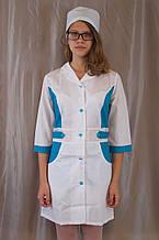 Медицинский женский белый халат, украшенный голубыми вставками.