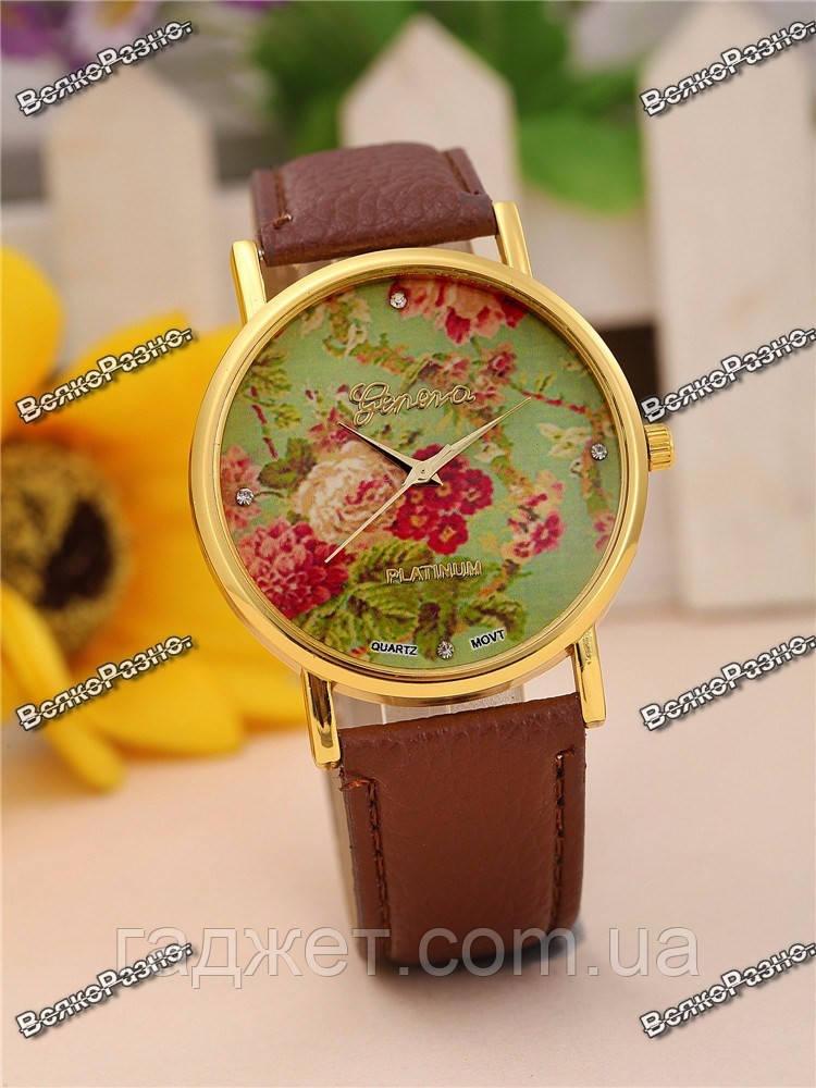 Часы Geneva с цветами на циферблате и коричневым ремешком.