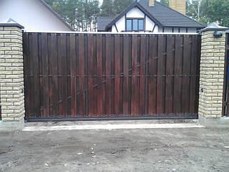 Автоматические откатные ворота с двусторонней вертикальной зашивкой сосновым брусом. Использована фурнитура для откатных ворот Rolling Center. Автоматика с системой bluebus NICE ROBUS (RB) 600