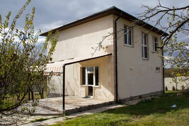 Тыльный фасад дома. Маркиз и под ним терраса облицованная керамической плиткой.