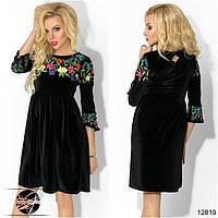 Элегантное платье прилегающего силуэта с клешеной юбкой в сборку на талии, декорированное цветочной вышивкой.