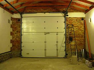 Секционные ворота Алютех промышленной серии с торсионными пружинами для больших гаражей и проемов. Встроенная калитка. Используется стандартный тип монтажа. Рекомендуется управление цепным редуктором или автоматическое.