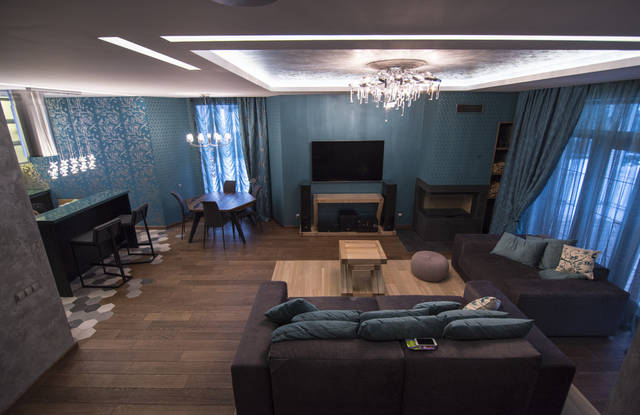 Гостиная. Вид на мягкий уголок с камином, домашним кинотеатром и кухню с обеденной зоной.