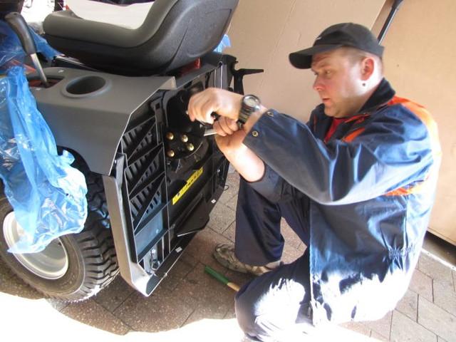 2 Механик Филипп устанавливает патрубок выброса травы на садовый трактор Хускварна 138