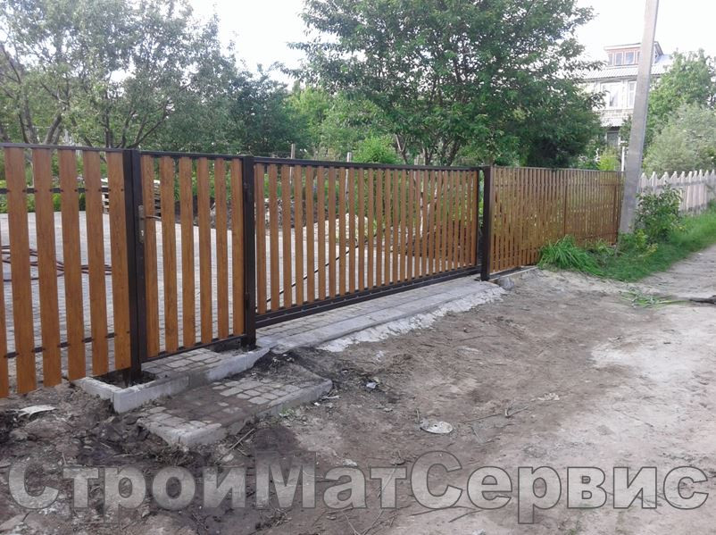 """В данном случае ограждение участка включало в себя забор, ворота на откатном механизме, калитка распашная из планок металлического евроштакетника с принтом """"золотой дуб"""" высотой 1,2м"""
