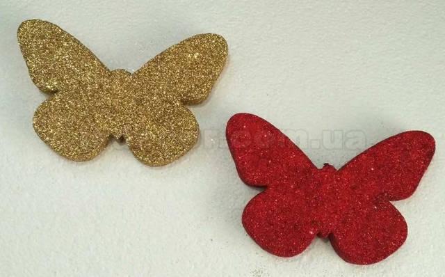 Бабочка из пенопласта покрытая глиттером золотого и красного цвета.