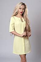 Молодежное светло-желтое платье-трапеция с украшением на вырезе