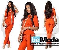 Необычный женский костюм из блузы с накладными карманами и облегающих брюк оранжевый