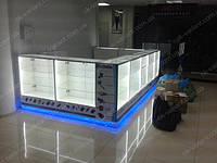 Торговый островок витрины под акссесуары для мобильных телефонов. Выполнен со стеклянных прилавков, с дверцами на замке. Стеклянные прилавки имеют стеклянный фасад и верх, стеклянные полки под наклоном и прямые.