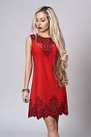 Яркое красное платье  украшено рисунком с камнями по горловине и низу