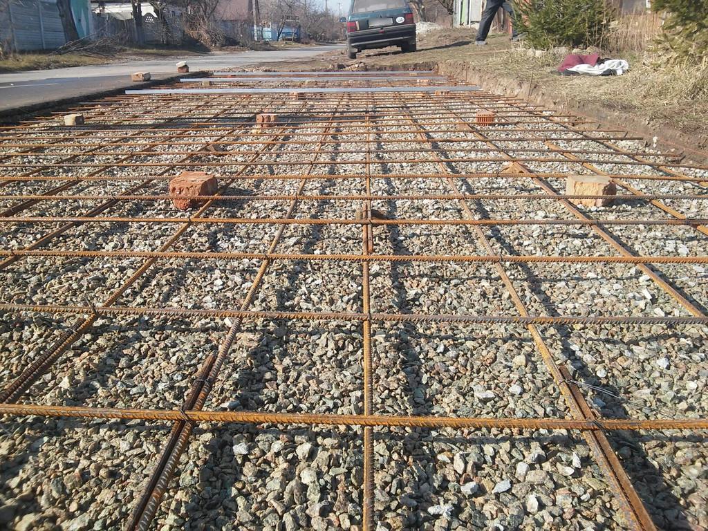Армирование находится на так называемом защитном слое - то есть внутри бетона, в нижней его части, примерно 25-40 мм от основания.