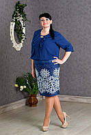 Элегантное женское платье украшено золотистой брошью синего цвета