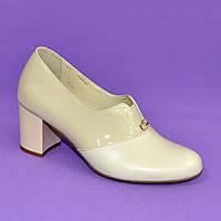 Женские классические бежевые туфли на каблуке, декорированы фурнитурой. Натуральная кожа и лак бежевого цвета