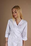 Красивый медицинский женский белый халат, украшенный вышивкой.
