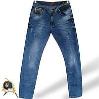 Зауженные мужские джинсы slim Mario батал светло-синего цвета с потёртостями.