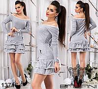 Трикотажное платье с открытыми плечами, декорировано воланами.